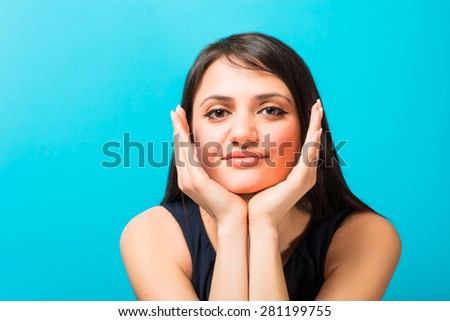 A young woman holds her hands face - stock photo