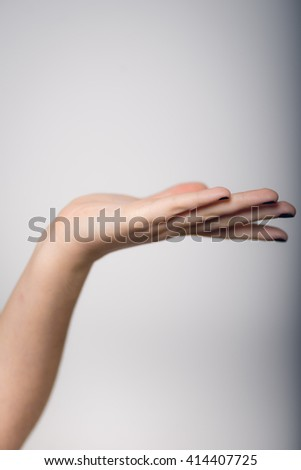 A young woman holds in the palm of your product or text in yellow clothes close-up isolated - stock photo
