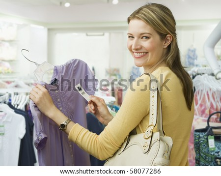 A young woman holds onto the price tag of a blouse while shopping.  She is smiling over her shoulder towards the camera.  Horizontal shot. - stock photo