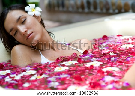 A young woman in a bath full of flowers - stock photo