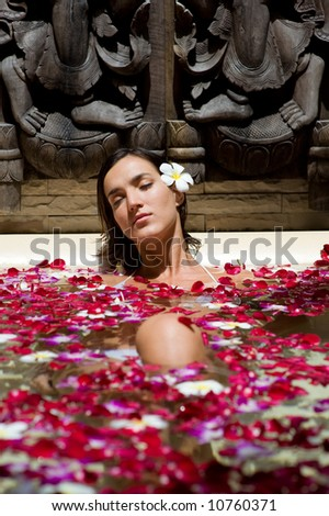 A young woman in a bath with petals and flowers - stock photo