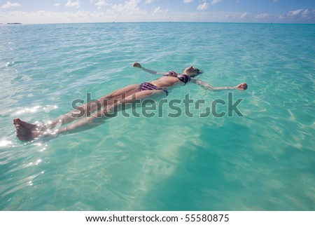A young woman in a bikini letting herself drift upon turquoise water - stock photo