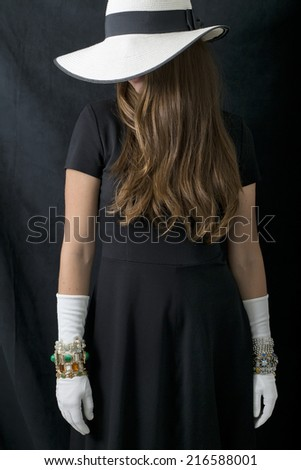 A young woman in a black dress, long white gloves, big floppy white and black hat and a lot of vintage bracelets on over the gloves. - stock photo