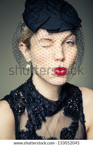 A young woman in a black veil winking - stock photo