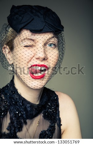A young woman in a black with her tongue out in a cheeky expression - stock photo
