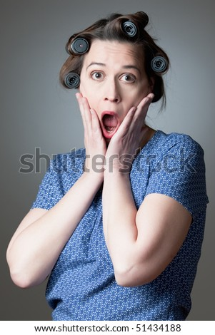 A young woman in a domestic role depicting astonishment - stock photo