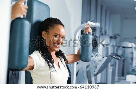 A young woman in a gym with a confident smile - stock photo