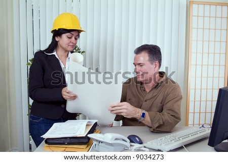 A young woman in a hardhat and a man looking over what appears to be construction plans.