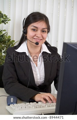 A young woman in a headset, smiling graciously while working the helpdesk. - stock photo