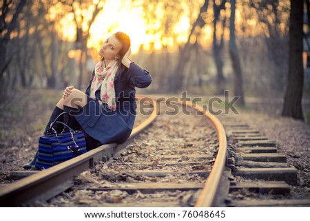 A young woman in a park near the railway at sunset - stock photo