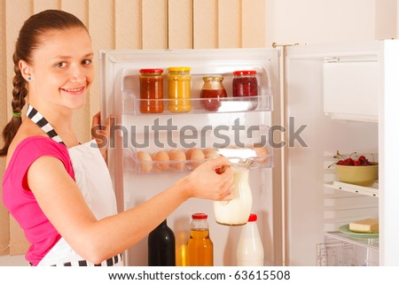 A young woman in a pinafore dress with milk in her hand in front of the open refrigerator. Food, milk, red wine and juice in the background. - stock photo