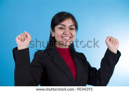 A young woman, in a posture of exhilaration, standing in front of a blue background. - stock photo