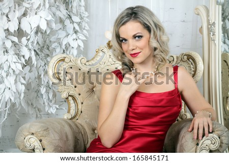 A young woman in a red dress, sitting in an old chair in the interior of the living room