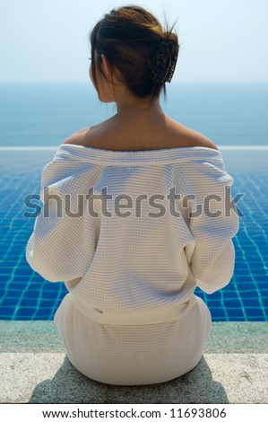A young woman in a robe looking at her pool and sea view - stock photo