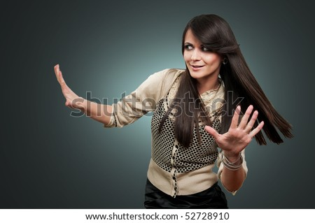 A young woman in a spotlight with her hands held out as if uncertain or defensive. Isolated on grayish background - stock photo