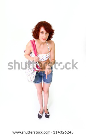 A young woman in a swimsuit and shorts showing thumb down - stock photo