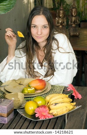 A young woman, in a white bathrobe, at a table of fruits, eating a mango. - vertically framed