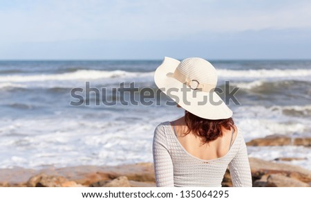 A young woman in a white hat is watching  waves. - stock photo