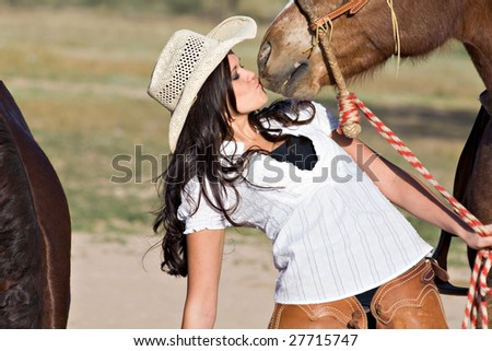 A young woman in chaps and a cowboy hat kisses her horse - stock photo