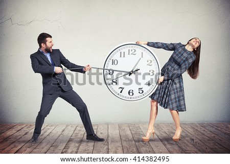 A young woman in checkered dress is intensively holding the big round clock while the man in dark business suit is pulling an hour-hand as if trying to slow down the time - stock photo