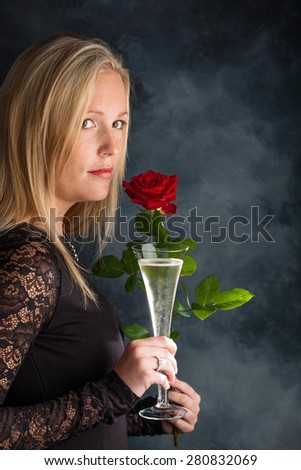 a young woman in evening dress with a red rose and a glass of sparkling wine or champagne. symbolic photo for valentine's day, romance and wedding - stock photo