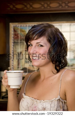 A young woman in her kitchen drinking coffee - stock photo