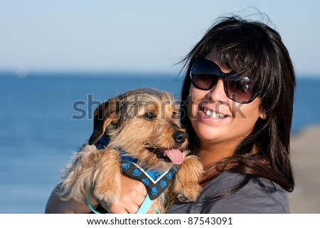 A young woman in her 20s by the sea shore holds a cute mixed breed beagle yorkshire terrier dog also called a Borkie. - stock photo