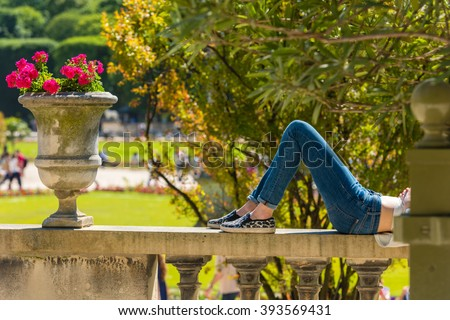 A young woman in jeans is lying and relaxing in a park on a sunny summer day