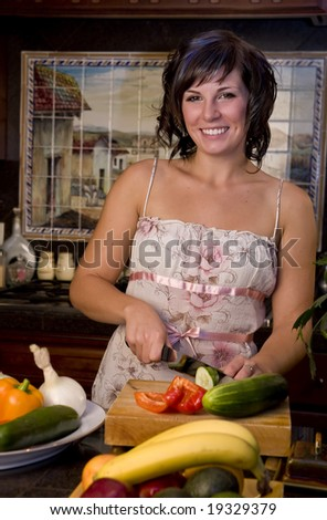 A young woman in the kitchen cutting vegetables - stock photo