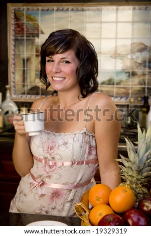A young woman in the kitchen drinking coffee - stock photo