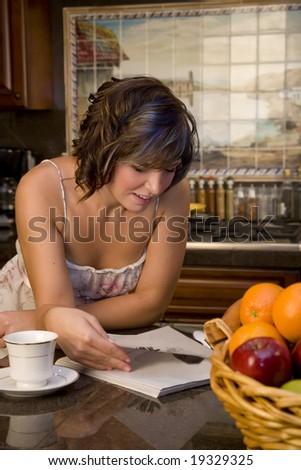 A young woman in the kitchen reading a magazine and drinking coffee - stock photo