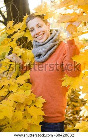 A young woman in the park in fall, relaxing and enjoying the sun.