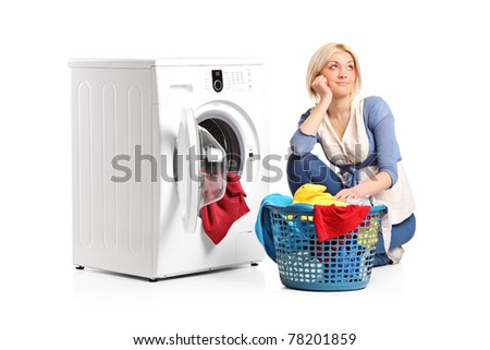 A young woman in thoughts with clothes seated next to a washing machine isolated on white background - stock photo