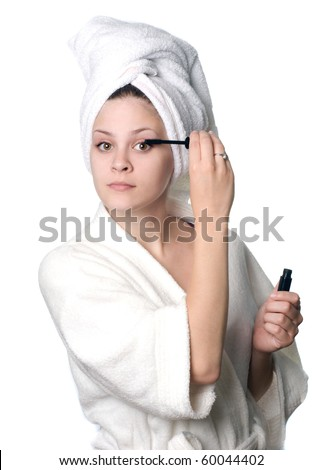 A young woman in white towel and robe applying make up after a shower.