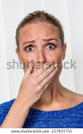 a young woman is afraid and acting scared - stock photo