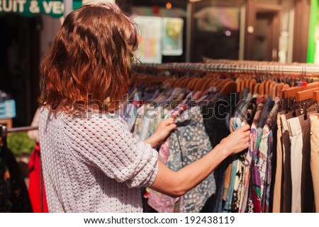 A young woman is browsing a rail of clothes at a street market - stock photo