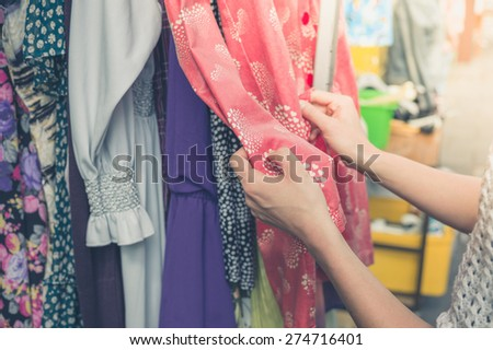 A young woman is browsing through clothing at a street market - stock photo
