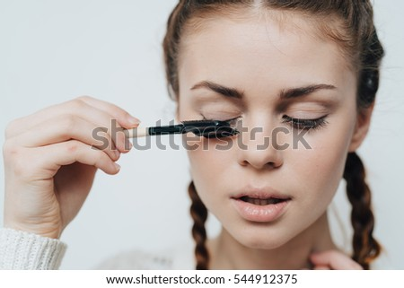 A young woman is brushing the eyelashes