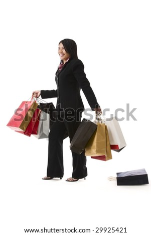 A young woman is carrying a lot of shopping bags without realize one bag is drop on the floor.