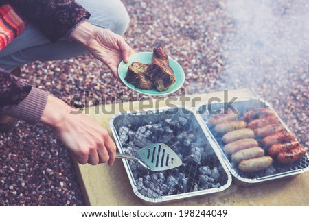 A young woman is cooking meat on a barbecue