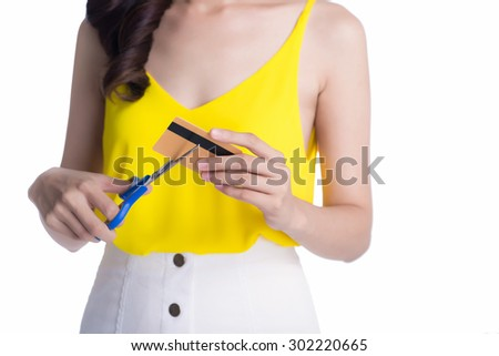 A young woman is cutting through her credit card with scissors. Vertical shot. - stock photo