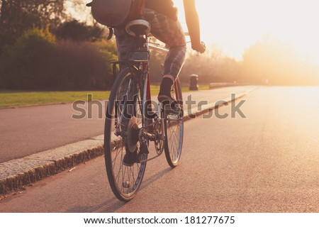 A young woman is cycling into the sunset in the park - stock photo