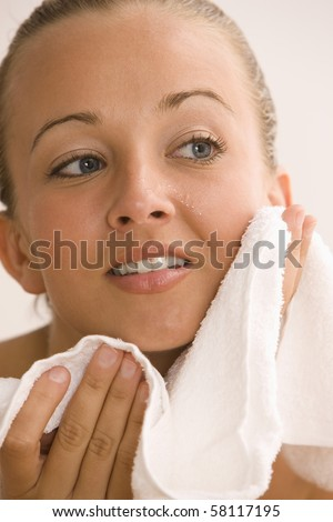A young woman is drying her skin with a towel after washing her face.  Vertical shot.