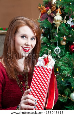 A young woman is excited and happy unwrapping her gift.
