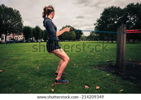 A young woman is exercising and working out with a resistance band in the park - stock photo