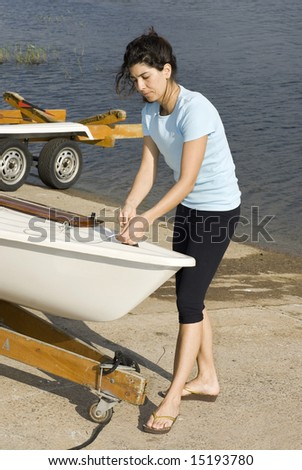 A young woman is  fixing something on her sailboat.  She is looking at the ropes in her hands.  Vertically framed shot. - stock photo