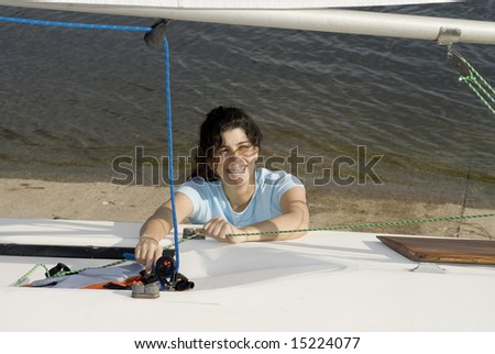 A young woman is  fixing something on her sailboat.  She is smiling and looking away from the camera.  Horizontally framed shot. - stock photo