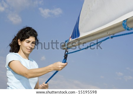 A young woman is fixing the sails on her sailboat.  She is looking away from the camera.  Horizontally framed shot. - stock photo