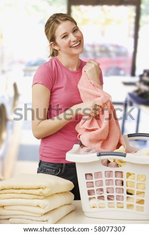 A young woman is folding laundry and smiling at the camera.  Vertical shot. - stock photo