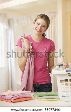 A young woman is folding laundry and smiling at the camera.  Vertical shot.